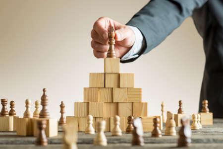 Geschäftsmann, der eine Schachfigur auf eine Pyramide von hölzernen Bausteinen in ein Konzept des Erfolgs und der Leistung in einen Abschluss herauf Ansicht seines Arms legt.