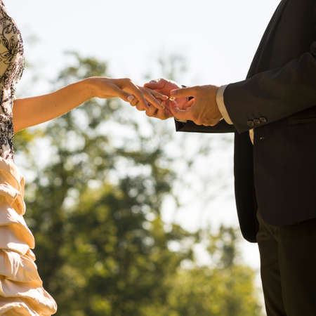 Groom marrying his bride outdoors in a park about to place a ring on the finger of her  hand, square format. Stock Photo