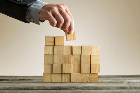 Businessman building a structure with wooden cubes on table surface on sepia toned background, concept with copy space.