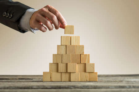 Nahaufnahme des Geschäftsmannes, der eine Pyramide mit leeren hölzernen Würfeln macht. Konzept der Unternehmenshierarchie.