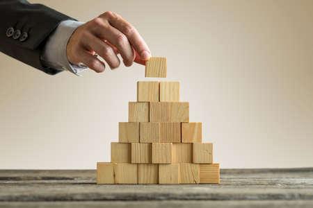 Primer del hombre de negocios que hace una pirámide con los cubos de madera vacíos. Concepto de jerarquía empresarial.