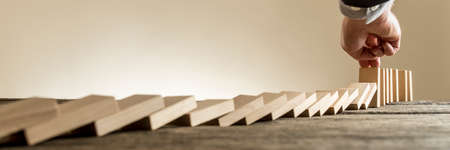 Male hand in business suit stopping domino effect of wooden blocks for concept about strategy and assistance, wide low angle view.