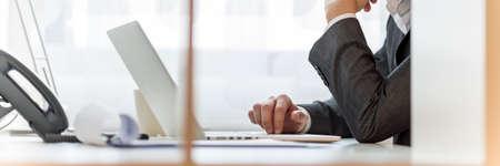 実業家は、彼のオフィス デスク トリミング テーブル、広い上に書類とパソコンに取り組んで表示に座っています。 写真素材