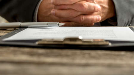 Businessman in a meeting sitting with clasped hands in a low angle close up cropped view over a clipboard with notes on an old wooden office desk or table. Stock Photo
