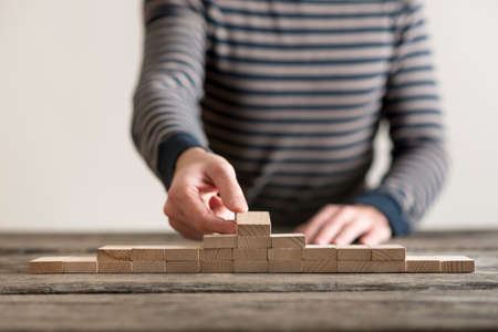 Man building a pyramid of wooden blocks on a rustic wood table in a concept of development and success in a low angle close up view of his hands.
