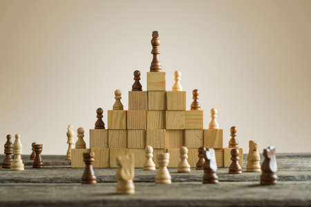 Business hierarchy; ranking and strategy concept with chess pieces standing on a pyramid of wooden building blocks with the king at the top with copy space. Фото со стока