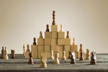 Jerarquía de negocios; ranking y concepto de estrategia con piezas de ajedrez de pie sobre una pirámide de bloques de construcción de madera con el rey en la parte superior con copia espacio. Foto de archivo