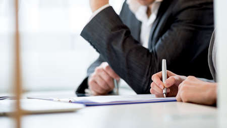 Business partners, sitting in an office checking a document or contract while signing it, cropped side view. Reklamní fotografie