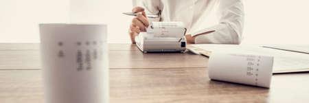 Lage hoek brede weergave van een vrouw die berekeningen uitvoert op een toevoegingsmachine of rekenmachine, conceptueel van boekhouding een boekhouding, getinte retro effect.
