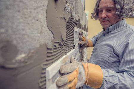 Retro stijlbeeld van een mens die een siertegel plaatst aan een lijm op een muur in een DIY-concept. Stockfoto