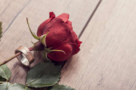 Top view of a single red rose with marriage or engagement ring around it on wooden table, retro effect faded look. Stock Photo
