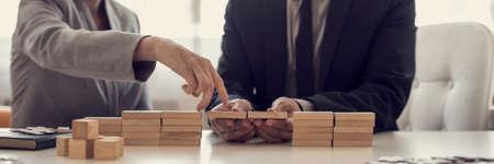 Retro beeld van zakenlui die problemen oplossen door bruggen met houten blokken te bouwen om een hiaat voor partner te overbruggen om haar vingers over in een conceptueel beeld te lopen. Stockfoto
