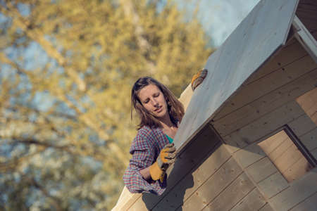 Woman in check shirt putting a wooden plank on roof of garden shed, a do-it-yourself construction, toned retro effect.