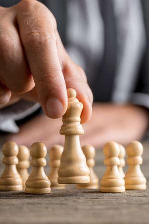 Homme jouant aux échecs déplaçant la pièce de la reine soulevant dans ses doigts dans une vue rapprochée avec des pions visibles derrière sur le bureau.