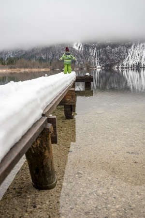 Rear view of a child in winter suit standing on a snowy pier on a lake Bohinj. Imagens