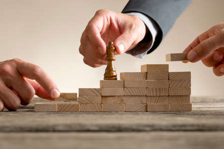 Business success and promotion concept with a businessman moving a chess piece up a series of steps formed by building blocks being put in place by his team in a close up view. Stock Photo - 83442995