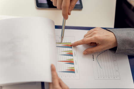 Two Business Partners Pointing at the Business Graph Representation on the Document While Discussing at the Table.