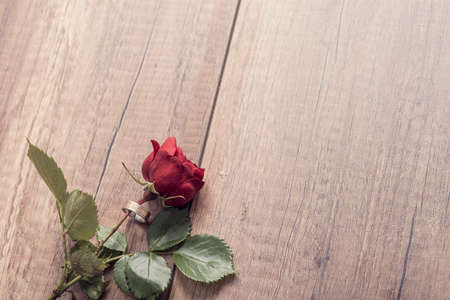 Retro style image of a red rose with engagement ring around it on wooden table with copy space. Stock Photo