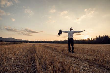 Retro image of a successful young businessman standing at the field with wide open arms and looking up in the sky.