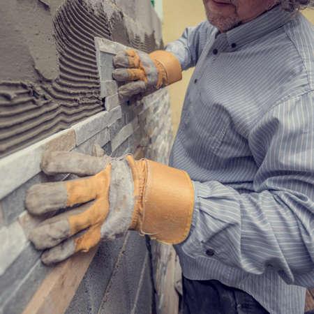 장식용 타일, 복고 효과 머 금고 벽을 바둑판 식 배열하는 동안 벽에 시멘트로 타일을 추진하는 보호 장갑에 육체 노동자의 근접 촬영 봐. 스톡 콘텐츠