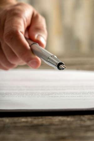 Close-up van mannelijke de inktpen die van de handholding u aanbieden om een ??document of een contract op een houten bureau te ondertekenen. Stockfoto - 83589530