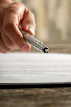 Closeup of male hand holding ink pen offering you to sign a document or contract on a wooden desk. Reklamní fotografie