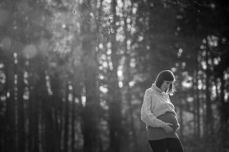 Grijstintenbeeld van een zwangere jonge vrouw die buiten in het bos staat, met haar handen met wazige bomen in de achtergrond en de kopie ruimte.