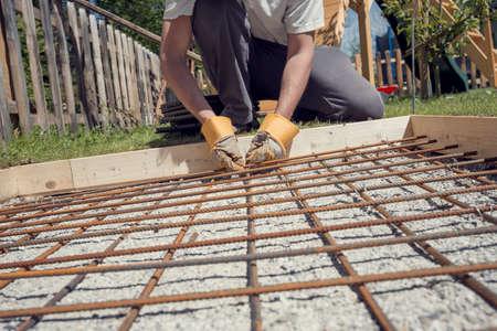 철조망 뒤뜰에서 구체적인 재단에 대 한 구멍에 보강으로 배치하는 펜 치와 함께 그들을 클리핑 하여 철강 막대 그물을 만드는 사람 복고 효과 머 금고