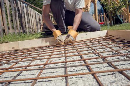Man making a net of steel bars by clipping them together with a wire and pliers placing it in as a reinforcement in a hole for a concrete foundation outside in backyard, retro effect faded look. Stock Photo