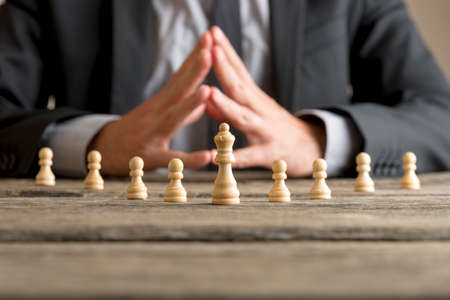 Businessman with clasped hands planning strategy with chess figures queen and pawns on an old wooden table. Stock Photo