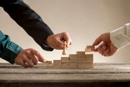 Il concetto di lavoro di squadra di affari con un uomo d'affari che muove una regina del pezzo degli scacchi su una serie di punti si è formato dai blocchi che sono messi sul posto dal suo gruppo. Archivio Fotografico - 85349169
