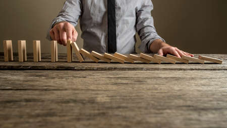 Front view of a businessman stopping domino effect with his finger. Security and insurance concept.