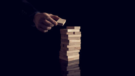 Male hand creating or building a tower of many wooden blocks over black background. Conceptual of career development and business vision or start up.