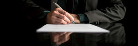 Wide cropped view of a businessman in business suit signing contract or document over black background. Stock Photo