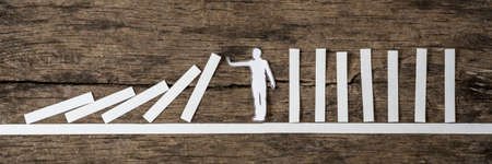 Man stopping the domino effect in a conceptual image of a white paper cutout silhouette on a rustic wood background.