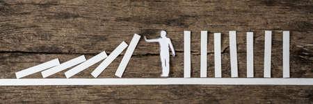 Homme arrêter le effet domino dans une image conceptuelle d & # 39 ; une silhouette de papier blanc sur un fond de bois rustique . Banque d'images - 86028321