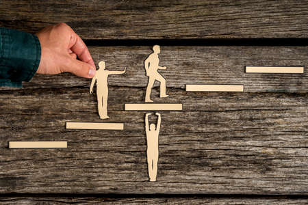 Teamwork concept on rustic wood with group of silhouette cutouts and a male hand helping a paper cutout of a climbing man. Stock Photo