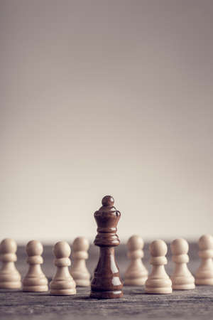 Retro effect faded and toned image of a black queen chess piece with white pawns standing on table.