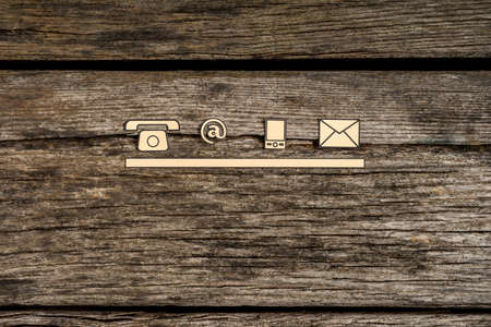 Contact and communication icons, telephone, at sign, mobile and mail, on textured rustic wooden boards. Archivio Fotografico