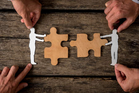 Group of four businessmen using paper cutout silhouettes of men holding puzzle pieces on rustic wood. Suitable for business teamwork concept. Reklamní fotografie