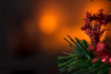 Christmas background with copy space and focus to small red stars on the branch of a Xmas tree. Imagens