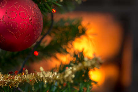 Christmas concept with a burning fire in the background and focus to red ball on the branch of a decorated Xmas tree.