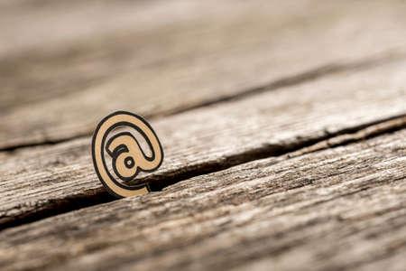 Pequeño En el símbolo esbozado con negro atrapado entre una grieta en la superficie de madera con bordes borrosos. Foto de archivo - 86801486