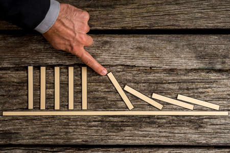 Businessman demonstrating stopping the domino effect using paper blocks. Stock Photo