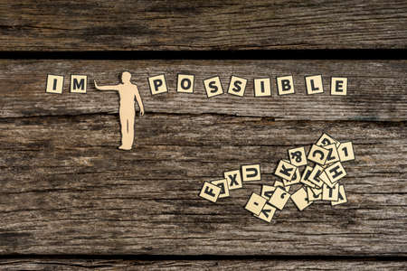 Figure diving impossible letter tiles sign into possible on wooden background with pile of scattered tiles.