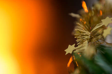 Christmas concept with a burning fire in the background and focus to small golden stars on the branch of a decorated Xmas tree. Imagens