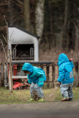 Two children wearing blue jackets playing outdoors in puddle.