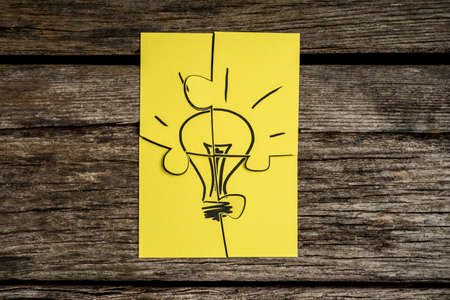 Four yellow pieces of a jigsaw puzzle bearing the image of a light bulb on a rustic wooden desk. Stok Fotoğraf