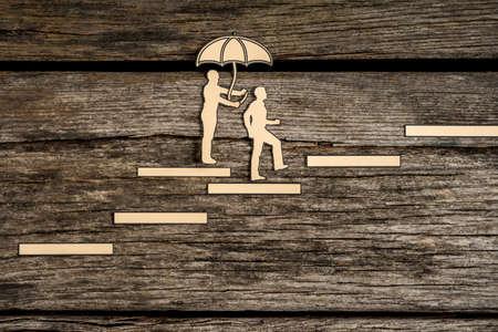 木材の背景を歩く他の傘を保持 1 つ階段を歩く小さな人シルエット。