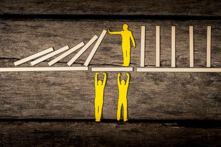 흰색 플랫폼에 서있는 동안 떨어지는 블록을 들고 작은 노란색 종이 사람이 두 개의 다른 노란색 피 규 어를 개최.